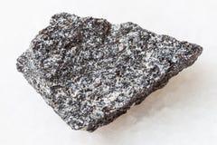 Raw nepheline syenite stone on white. Macro shooting of natural mineral rock specimen - raw nepheline syenite stone on white marble background Stock Photography