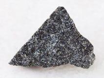 Raw olivinite stone on white. Macro shooting of natural mineral rock specimen - raw olivinite stone on white marble background from Kovdor region, Kola Peninsula Stock Photography