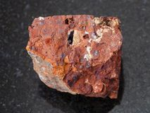 Raw red bauxite stone on dark background. Macro shooting of natural mineral rock specimen - raw red bauxite stone on dark granite background stock photos
