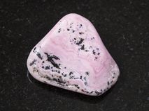 Raw rhodochrosite gem on dark background. Macro shooting of natural mineral rock specimen - raw rhodochrosite gem on dark granite background from Peru Stock Photography