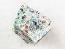Rough amazonite granite stone on white. Macro shooting of natural mineral rock specimen - rough amazonite granite stone on white marble background Royalty Free Stock Image