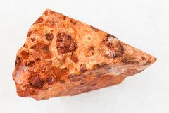Rough bauxite ore on white. Macro shooting of natural mineral rock specimen - rough bauxite ore on white marble background from Ukraine Stock Image