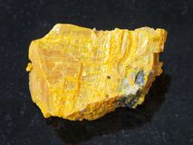 Rough native orpiment stone on dark Stock Images