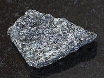 Rough nepheline syenite stone on dark. Macro shooting of natural mineral rock specimen - rough nepheline syenite stone on dark granite background Stock Image