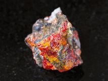 Rough Realgar crystals on stone on dark Stock Photography