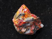 Rough Realgar stone on dark background Royalty Free Stock Photography