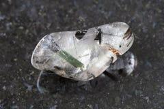Tumbled quartz gemstone with Tourmaline on dark Royalty Free Stock Images