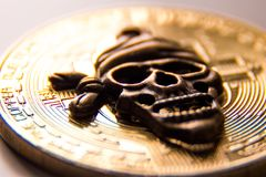 Macro shooting of the symbol of the pirate skull against the background of the gold coin of the crypto currency. The royalty free stock photo