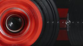 Macro shot of analog audio tape rewinding. Closeup macro shot of a red rewinding vintage compact audio cassette with magnetic analog tape rewinding in deck stock video