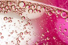 Macro shot of backlit liquid with small bubbles in it over colored background royalty free stock photo