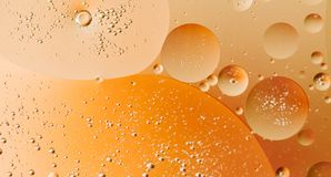 Macro shot of backlit water-oil emulsion over colored background. Gas-liquid-liquid emulsion. Multiphase mixture. Tiny gas bubbles inside larger oil bubbles stock images