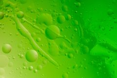 Macro shot of backlit water-oil emulsion over colored background. Tiny gas bubbles inside larger oil bubbles inside water base. Long drops of water and stock photography
