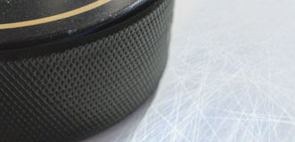 Macro shot of black hockey puck on ice rink Royalty Free Stock Photography
