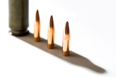 Macro shot of bullet. Casings on a white studio background. Sleeve casts a shadow on the tough end of which is shiny copper bullet Stock Image