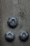 A macro shot of a bunch of blueberries on a dark vintage slate Stock Photo