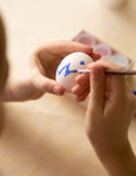 Macro shot of child painting Easter egg with brush Royalty Free Stock Images