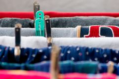Macro shot of clothes drying on a hanger. With clips and a mix of colorful textiles Stock Photos