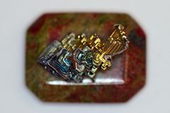 Macro image of a colorful bismuth crystal on top of a polished unakite stone royalty free stock images