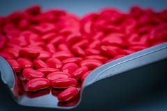 Macro shot detail of red kidney shape sugar coated tablet pills. On stainless steel drug tray Stock Images