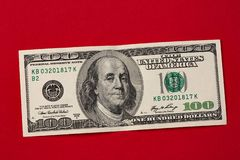Macro shot of a 100 dollar bill on red background stock photo