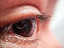 Macro shot of an eye and reflection of camera lens