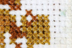 Macro shot fragment embroidery pattern brown thread handmade embroidery, pattern in cross-stitch style on white fabric Stock Photo