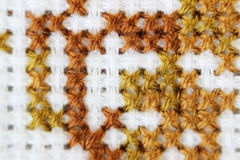 Macro shot fragment embroidery pattern brown thread handmade embroidery, pattern in cross-stitch style on white fabric Royalty Free Stock Images