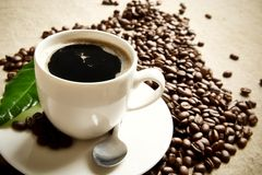 Macro shot of frothy coffee with green leaf on linen cloth Royalty Free Stock Photos