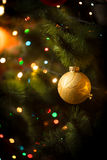 Macro shot of golden ball and light garland on Christmas tree Royalty Free Stock Photos