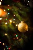 Macro shot of golden ball and light garland on Christmas tree Royalty Free Stock Photos