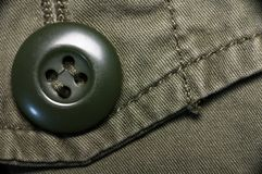 Macro shot of green textured garment. Macro shot of green textured army garment with button Royalty Free Stock Photography