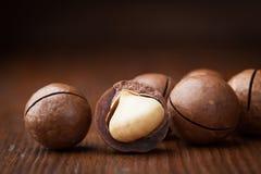 Macro shot of macadamia nuts on wooden table. Royalty Free Stock Image