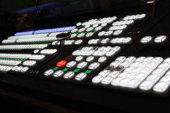 This is a macro shot of a mixing sound video tv radio station control board. Very cool shot of keys and controls lighting up in the dark. Communications Stock Photo