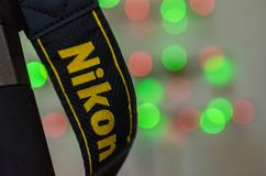 Macro shot of Nikon camera strap. Against bokeh Christmas lights background Stock Images