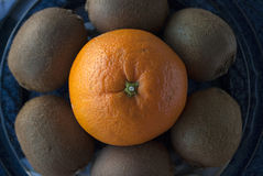 Macro shot of an orange surrounded by kiwis. Overhead macro photography of a round shaped composition of natural fresh fruits: orange and kiwis on a blue platter stock images