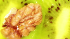 Macro shot: a piece of walnut is being placed in the fresh kiwi stock video