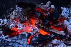 Macro shot of glowing ember in a fireplace. Macro shot of piled up charcoal with orange and red glowing ember in a fireplace Stock Photos
