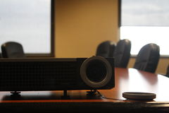 Macro shot of projector with cap off in conference room office setting. This is a macro shot of a projector with cap off in conference room office setting. Lens Stock Photography