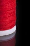 Macro shot of red bobbin thread  on black Stock Images
