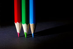 Macro Shot of Red, Green and Blue Sharpened Colorful Pencils Against Black Background Stock Images