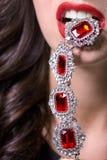 Macro shot. Red lips with jewelery pendant Stock Photos