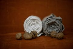 Macro shot of rolled, folded snow white and grey natural linen sauna and bath towels. Next to small walnuts on orange background, on massage table. Beautiful Stock Photography