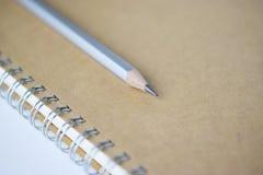 Macro shot of sharpened pencil on brown notebook. Macro shot of sharpened pencil on a brown notebook royalty free stock photo
