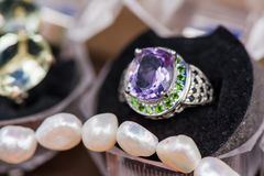 Macro shot of silver engagement ring in gift box on colorful, sparkling background. Ring made of sapphire, amethyst, chrome diopside stones. Healing, natural Royalty Free Stock Images