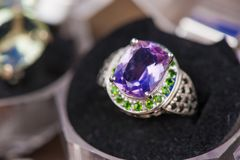 Macro shot of silver engagement ring in gift box on colorful, sparkling background. Ring made of sapphire, amethyst, chrome diopside stones. Healing, natural Stock Photo