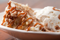 Macro shot of a slice of maple walnut cinnamon cake. Maple Walnut Cinnamon Cake topped with vanilla ice cream and drizzled with a decadent caramel sauce Royalty Free Stock Photography