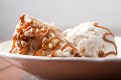 Macro shot of a slice of maple walnut cinnamon cake white background. Maple Walnut Cinnamon Cake topped with vanilla ice cream and drizzled with a decadent Royalty Free Stock Photos