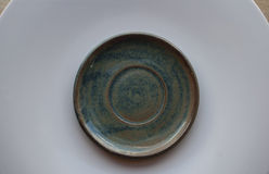 Macro shot of the small blue saucer on a large white plate on a wooden table Royalty Free Stock Images