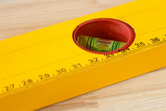 Macro shot of a spirit level with ruler on a wooden background Royalty Free Stock Images
