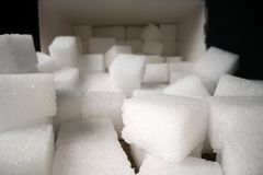 Macro shot of sugar cubes next to carton box on wooden table. Unhealthy food sweetener, sweet crystal cubes.  stock photo